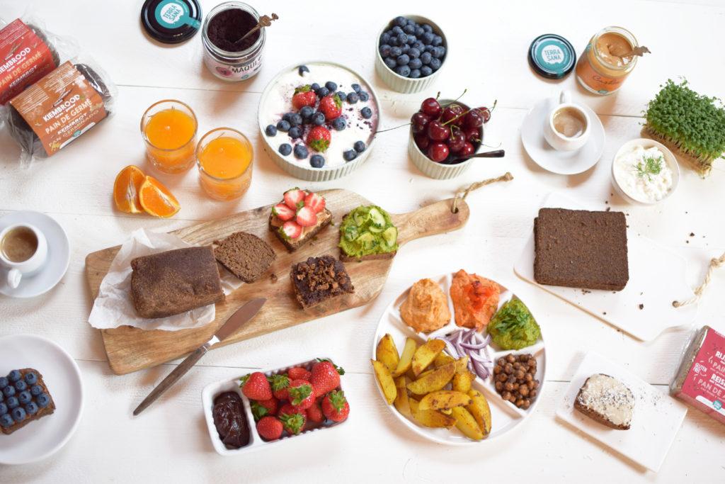 ontbijttafel met kiembrood, kokosyoghurt met fruit en hummus